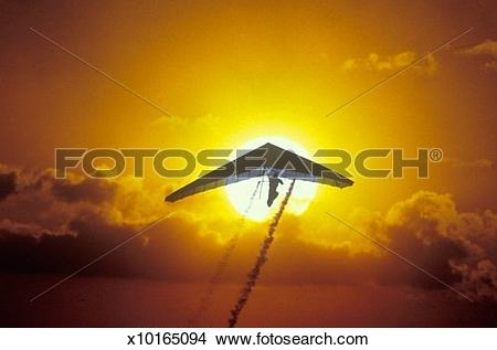 Stock Photo of Solar Sailing Hang Gliding in sunset silhouette.