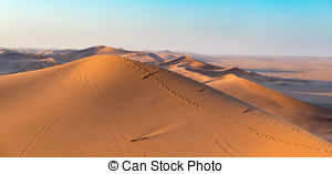 Stock Photo of Tourist walking in the majestic Namib desert.