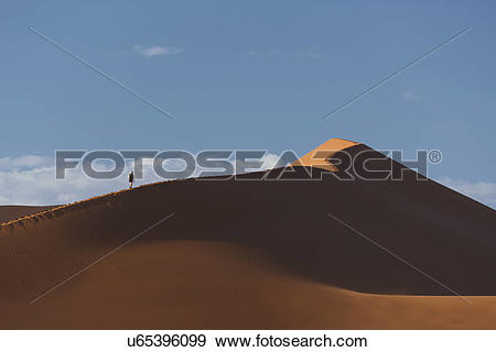 Stock Photograph of Silhouetted man climbing giant sand dune.