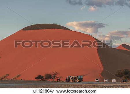 Picture of Large group of tourists climbing giant sand dune.