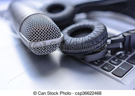 Stock Image of Microphone and headphones on laptop. sound editing.