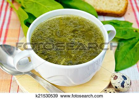 Stock Photograph of Soup of greens on the fabric with a spoon.