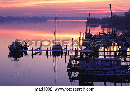 Stock Photo of Sailboats in small marina at sunrise on still water.