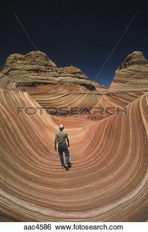 Stock Images of Man walking in the Navajo sandstone at Colorado.