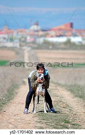 Stock Photo of Young attractive woman hugs her Spanish greyhound.