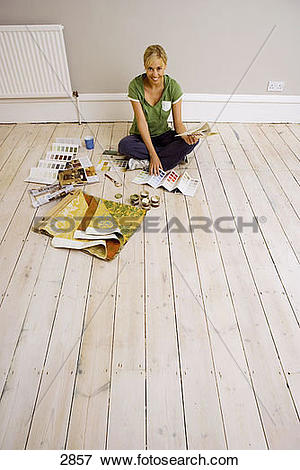 Picture of Woman decorating at home, sitting on floor in sparse.