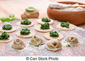 Stock Photography of Dough circle filled with spinach ready to.