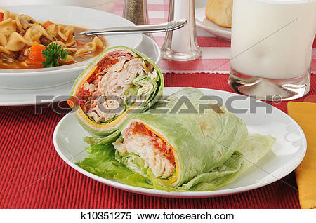 Stock Image of Turkey club sandwich wrapped in a spinach tortilla.
