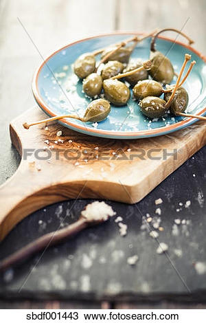 Stock Photo of Pickled caperberries, Capparis spinosa, with sea.