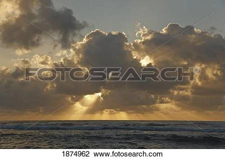 Stock Photo of sun rays spread from clouds at sunrise over the.