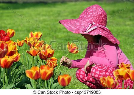 Pictures of little girl smell tulip flower spring scene.