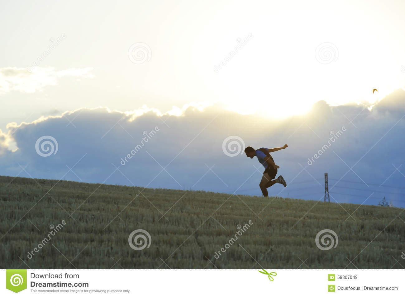 Profile Silhouette Of Young Man Running In Countryside Practicing.