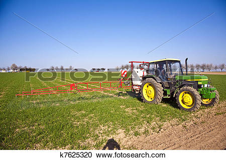 Stock Photography of tractor on field sputtering pest protection.