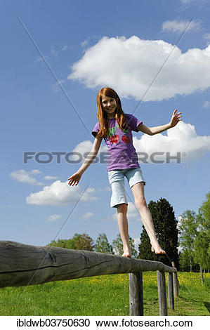 """Stock Photography of """"Girl, 11 years, balancing on a wooden."""