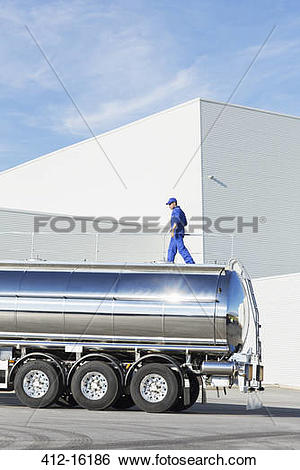 Stock Images of Worker walking on platform above stainless steel.