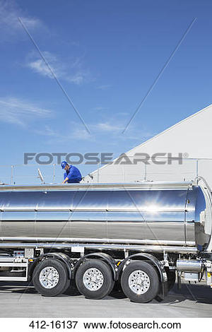 Picture of Worker on platform above stainless steel milk tanker.