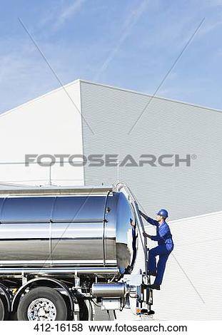 Pictures of Worker climbing ladder at back of stainless steel milk.
