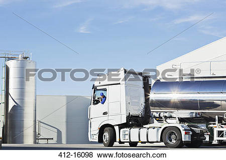 Pictures of Truck driver parking stainless steel milk tanker.