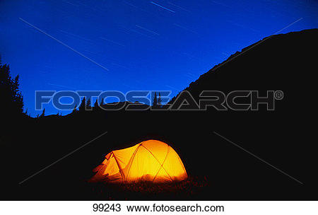 Stock Photo of Glowing tent with star trails in the mountains.