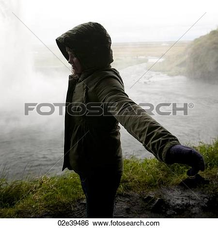 Stock Images of Girl in hooded coat standing in profile with arms.