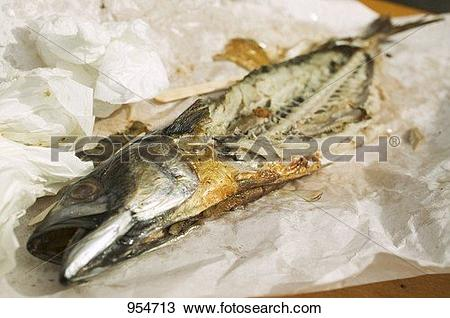 Stock Photo of Remains of Steckerlfisch (skewered fish) on paper.