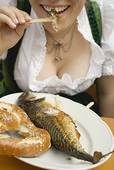 Stock Photo of Woman eating Steckerlfisch (skewered fish) with.