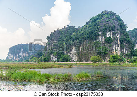 Stock Photos of A steep small mountain in the middle of green.