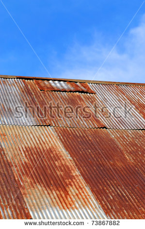 Old Corrugated Tin Roof Is Rusting And Patched. Sunny Blue Sky And.
