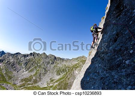 Stock Photographs of Caucasian male climber climbing a steep wall.