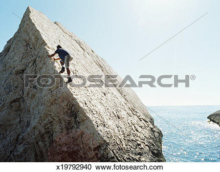 Stock Photography of Italy, Sardinia, man climbing steep boulder.