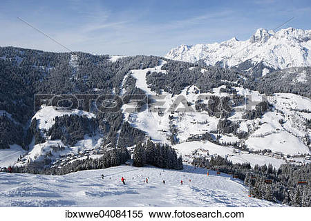 """Stock Image of """"Skiers on slope in front of mountains, view to the."""
