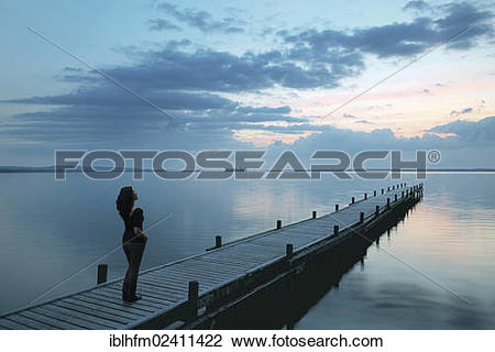 "Stock Photo of ""Young woman standing on boat dock on the lake."