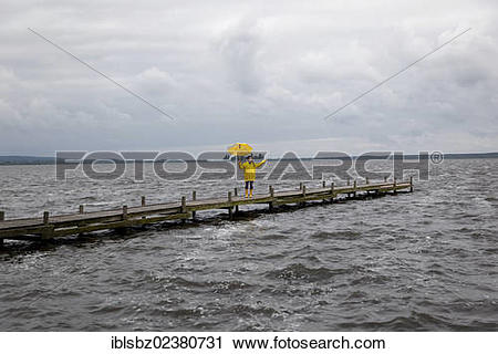"Stock Photography of ""Woman walking on a jetty in the rain holding."