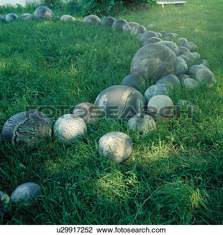 Stock Photo of Stone balls in long grass in large country yard.