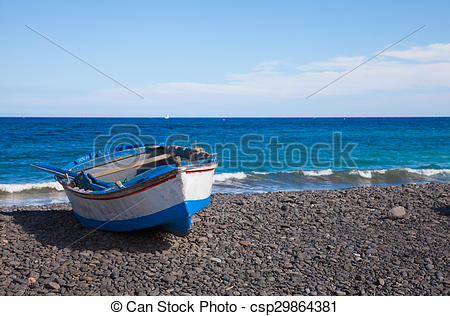 Pictures of Fuerteventura, old boat on black volcanic stone beach.