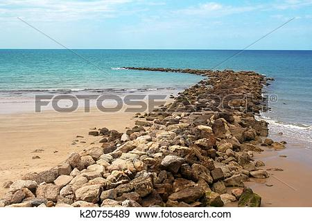 Stock Photograph of stone breakwater and sandy beach.