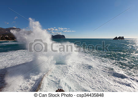 Stock Photo of Stone breakwater with breaking waves. Adriatic Sea.