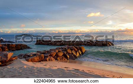Stock Illustration of Warm sunset stones in the sea k22404965.