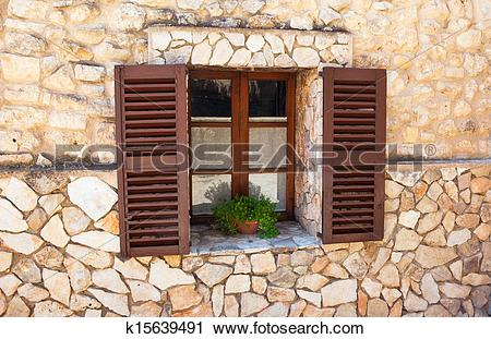 Stock Photography of Old Shutter windows with a pot of flowers on.