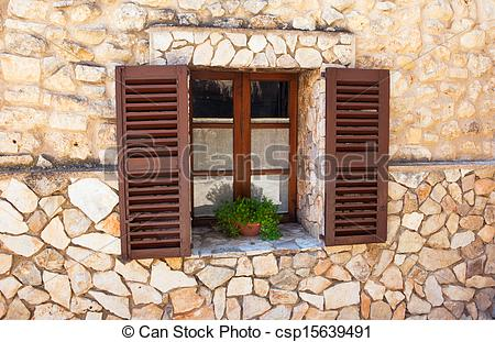 Stock Photographs of Old Shutter windows with a pot of flowers on.
