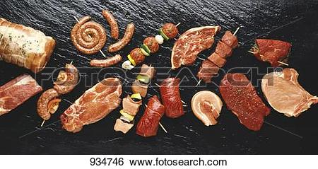 Stock Images of Assorted meats and sausages on hot stone grill.