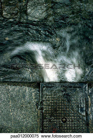 Stock Image of Water pouring into gutter, high angle view, close.