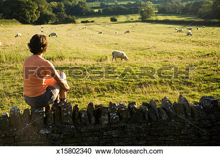 Stock Photography of Woman, sitting on stone fence overlooking.