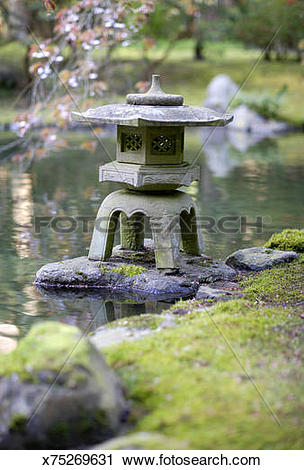 Stock Photography of Ornamental stone pagoda in garden pond.