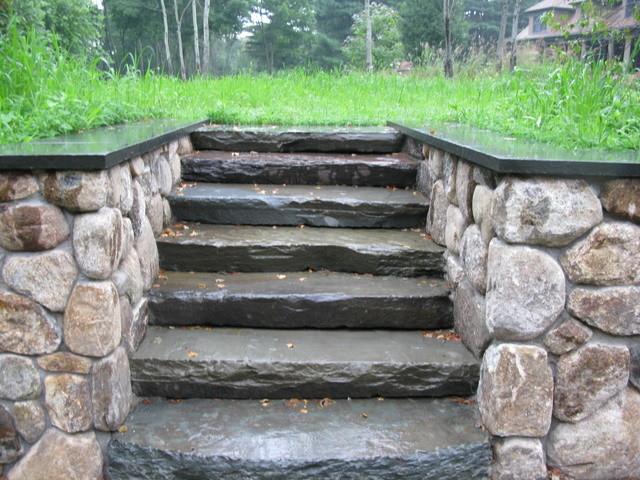 Bluestone rough hewn steps set into stone retaining wall.