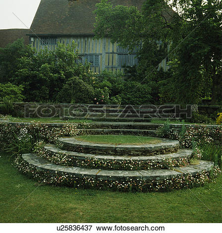 Picture of Curved stone steps in large country garden in front of.