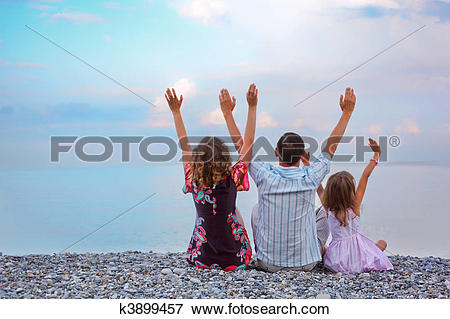 Picture of Happy family with little girl sitting on stony beach.