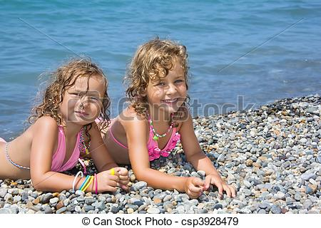 Stock Photographs of two pretty little girls lying on stony beach.