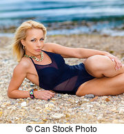 Stock Images of girl in a black bikini swimsuit on the stony beach.
