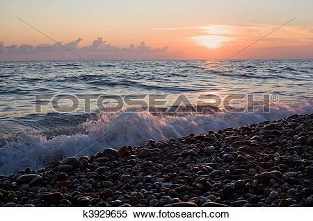 Stock Image of Sea coast with waves on sunset, Stony beach.